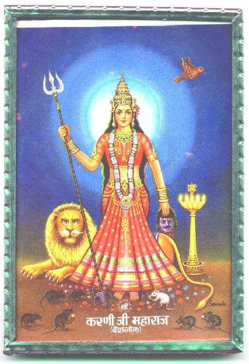 Hindu-style icon of crowned woman in red dress standing in front of a reclining lion, carrying a trident and surrounded by several brown rats and one white one, who are eating sweets off the floor by her feet